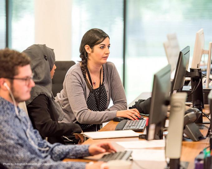 3 junge Menschen im Büro, die junge Frau im Mittelpunkt sieht offensichtlich mit Kontaktlinsen entspannt auf den Screen.