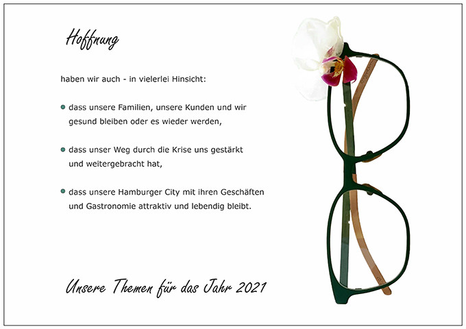 Der BELLEVUE-Wunsch Hoffnung mit einer grünen Brille von Orgreen und einer angesteckten Blüte.