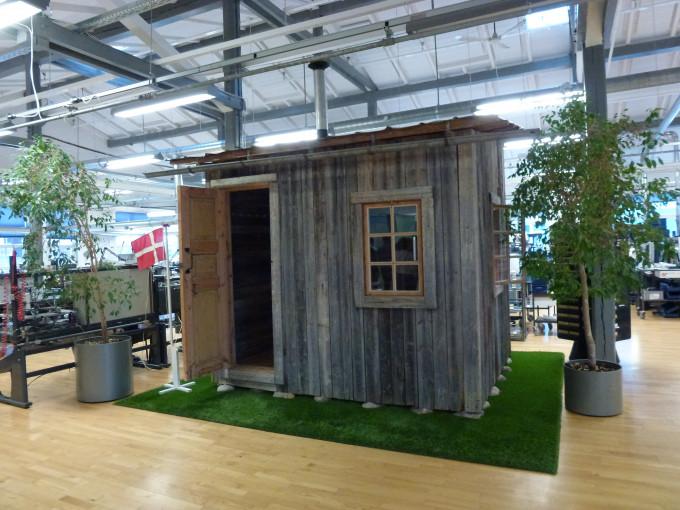 Eine sehr kleine nordisch anmutende Holzhütte auf künstlichem Rasen inmitten der Produktionshalle der Lindberg Manufaktur in Aarhus, Dänemark.