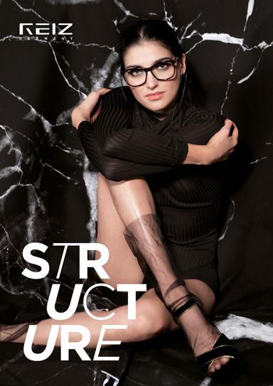 Ein Frau mit einer großen, dunklen Brillenfassung von REIZ sitzt mit dunklem Pullover und nackten Beinen vor einer marmorierten Wand.