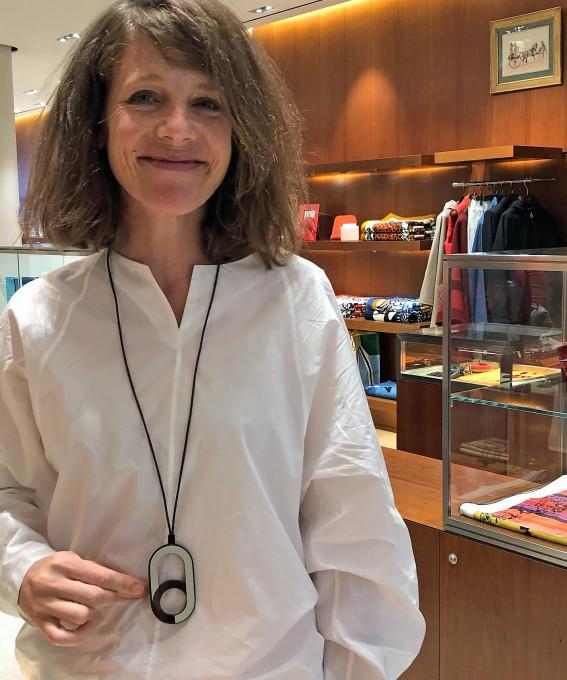 Veronika Wildbruber mit einer lange Kette aus Lederband und einem schlichten Ornament aus Büffelhorn, das sie für die Hermés Modeschmuck-Kollektion entworfen hat. Sie steht im Hamburger Showroom von Hermés.