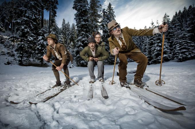 Roland und Bernhard Wolf mit ihren Mitgründern in Vintage-Skiausrüstung am verschneiten Berg.
