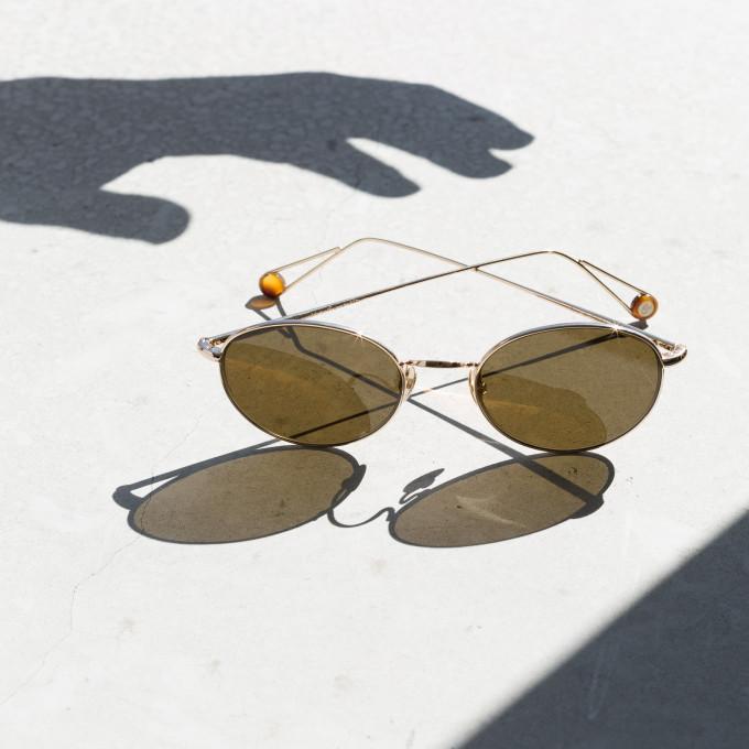 Eine Ahlem Sonnenbrille aus Metall, in greller Sonne mit Schattenspiel und dem Schatten einer Hand, die nach ihr greifen will.