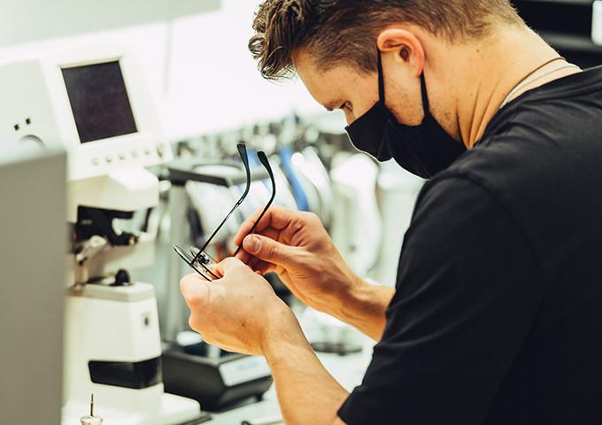 Augenoptiker mit Corona-Maske in der Werkstatt beim Ausrichten einer Brille.
