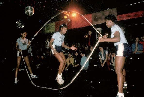 3 Mädchen in Sport-Outfit mit einem doppelten Springseil in einer Springseil-Figur mit dem Namen Double Dutch.