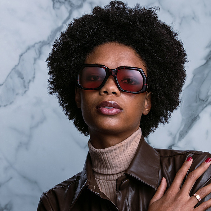 Frauenportrait mit schwarz-roter Sonnenbrille in extravaganter Form von Jacques Marie Mage.