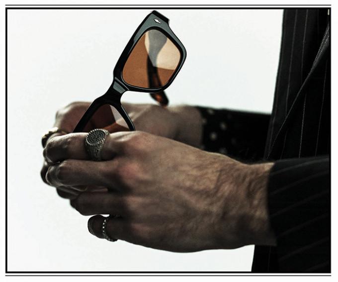 Eine schwarze Fellini Sonnenbrille gehalten von 2 Männerhänden mit auffälligem Schmuck