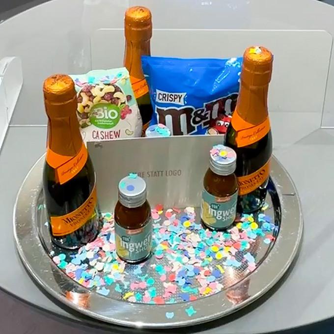 Ein Tablett mit 3 Piccolo Flaschen Sekt, ein paar Süßigkeiten und Konfetti steht als Neujahrsgruß auf dem Tisch als Willkommensgruß zum Neuen Jahr.