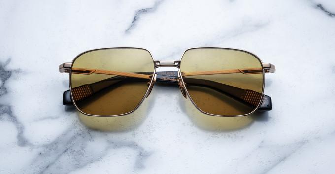 Eine klassische Metall-Sonnenbrille, Modell Sexton, mit gelb-braunen Brillengläsern auf Marmor.