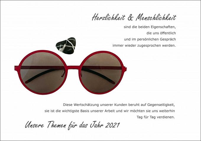 Der BELLEVUE-Wunsch Herzlichkeit und Menschlickheit mit einer großen runden roten Sonnenbrille von Orgreen.