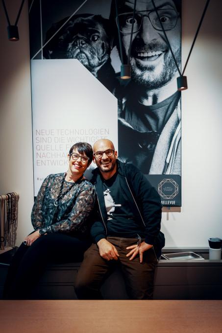 Roland Wolf sitzt mit Karin Stehr auf einem Tresen bei BELLEVUE. Dahinter das Großportrait von ROLF Spectacles.