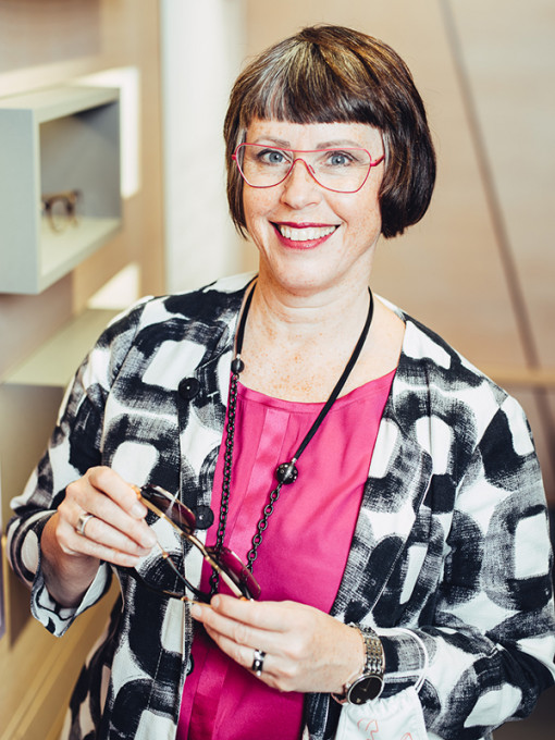 Karin Stehr, Gründerin und Inhaberin von BELLEVUE in einer Beratungssituation mit einer Brille in den Händen.