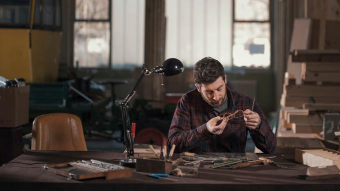 Bernhard Wolf demonstriert die Endkontrolle einer manufakturgefertigten Holzbrille.