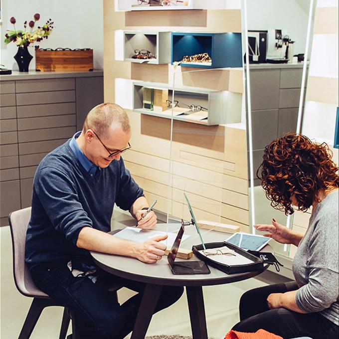 Carsten Werner und eine Kundin beim Durchführen der digitalen Sehanalyse auf einem iPad an einem Beratungstisch im Geschäft.