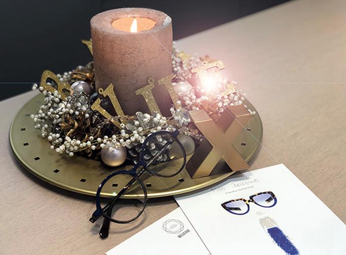 Adventsgesteck mit einer dicken brennenden Kerze, einer Brille und einem Geschenkgutschein mit einem Frauenmotiv.
