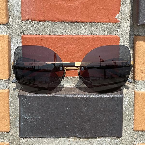 Randlose Brille mit goldener Garnitur und Schmetterlingsform vor einer Ziegelwand.