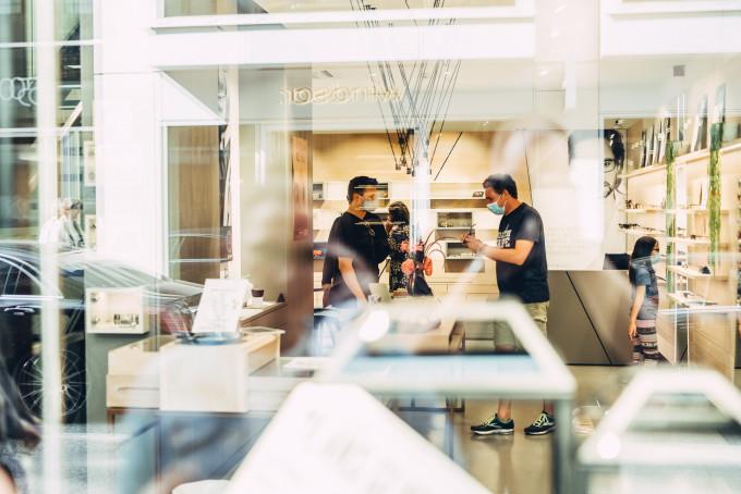 Blick durch die Schaufensterscheibe in das Geschäft mit einer Beratungssituation in lockerer Atmosphäre