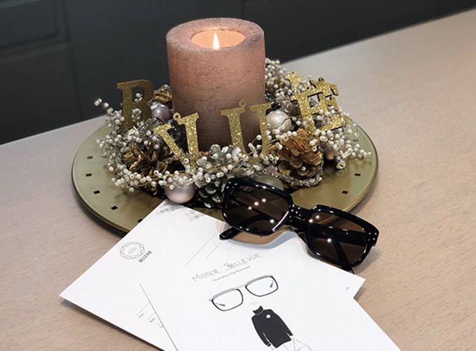 Adventsgesteck mit brennender Kerze und einer maskulinen Sonnenbrille sowie Geschenkgutschein mit einem Männermotiv.