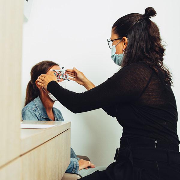 Augenoptikerin setzt einer Kundin die Prüfbrille für den Sehtest auf.