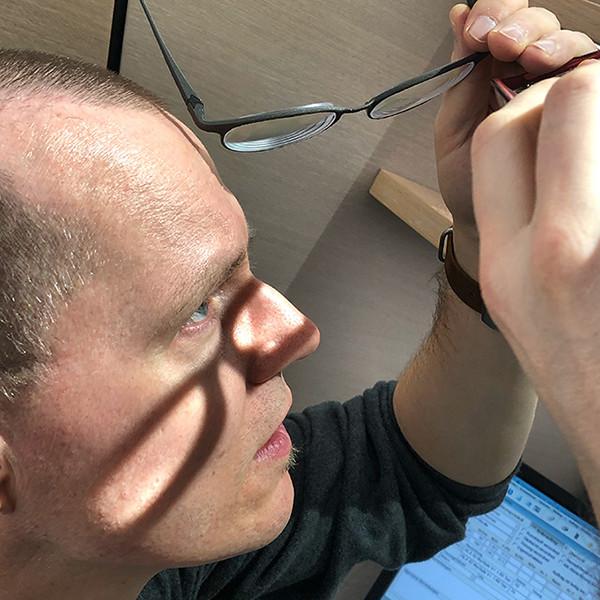 Augenoptiker in Nahaufnahme beim Prüfen von Brillengläsern.