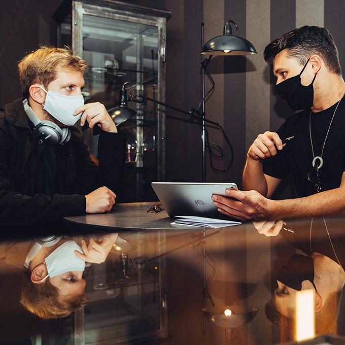 Sash Starowoitow und ein Kunden mit Masken im konzentrierten Gespräch an einem einzelnen Beratungsplatz.