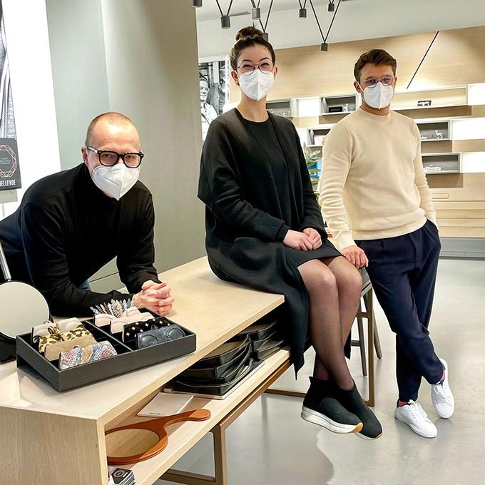 2 Optiker und eine Optikerin aus dem BELLEVUE Team stehen und sitzen am mittleren Beratungstisch und erwarten neue Kunden.