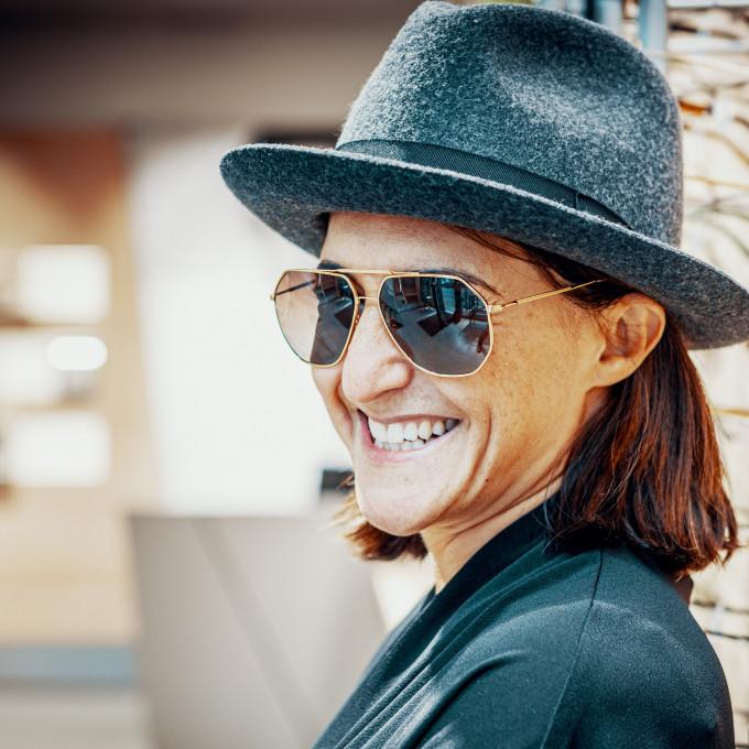 Claire Goldsmith, Inhaberin der traditionsreichen Marke Oliver Goldsmith mit maskulinem Hut und Sonnenbrille im Geschäft von BELLEVUE.