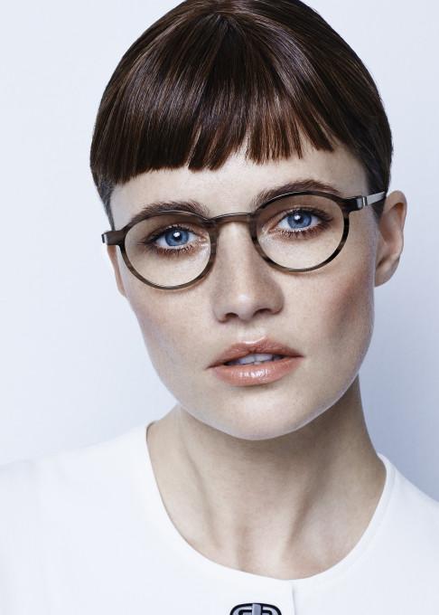 Portrait einer Frau mit einer modernen runden Brille aus echtem Büffelhorn mit Titanbügeln.