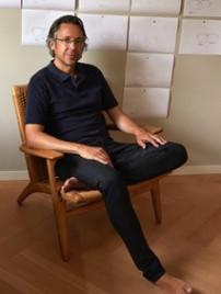 Sven Götti, Desinger der Götti Brillen in entspannter Haltung auf einem Holzsessel in seinem Atelier.
