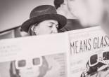Claire Goldsmith mit Hut, halb verdeckt von einer Zeitung mit Fotos ihrer Oliver Goldsmith Kollektion.