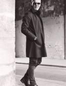 Franz Reutter, Gründer und heute alleiniger Inhaber von REIZ, mit Mantel, Jeans und Sonnenbrille.