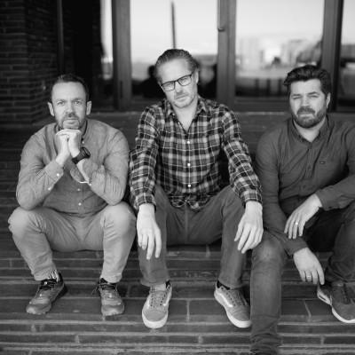 Gregers Fastrup, Henrik Orgreen und Tobias Wandrup, das Inhaber Trio von Orgreen sitzen auf einer Außentreppe.