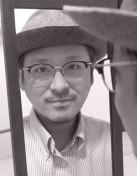Yuichi Toyama, Gründer und Inhaber der Kollektion Yuichi Toyama mit leichtem Lächeln in einen Spiegel blicken.d