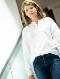 Veronika Wildgruber in Jeans und weißer Bluse auf der Treppe im Geschäft von BELLEVUE