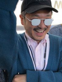 Yuichi Toyama auf der Messe mit total weißer, undurchsichtiger Brille, winkend und lächelnd.