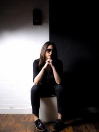 Claire Goldsmith, Inhaberin der traditionsreichen Firma Oliver Goldsmith Sunglasses, sitzt nachdenklich auf einem Hocker.