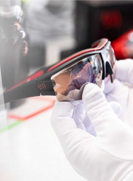 evil eye Sportbrille, gehalten von 2 Händen mit weißen Handschuhen in der Endkontrolle.
