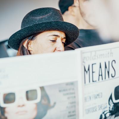 Claire Goldsmith, Inhaberin von Oliver Goldsmith Sunglasses, liest in einer Zeitung die ausschließlich über ihre Kollektion berichtet.