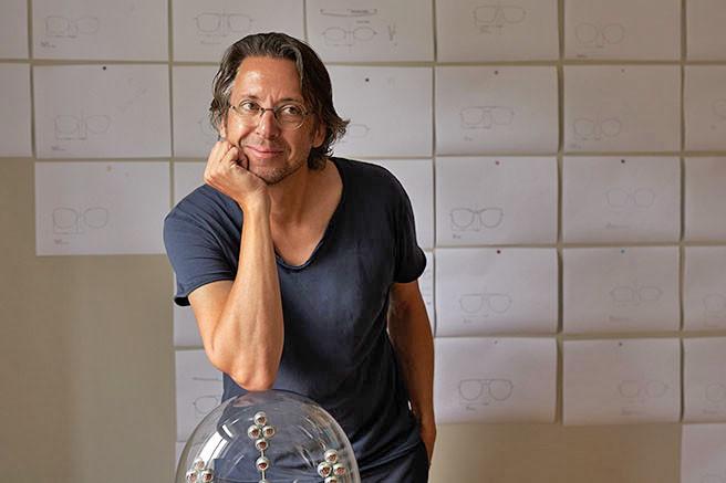 Sven Götti, Gründer und Inhaber von Götti aus Zürich vor einer Pinnwand mit Brillen Skizzen.