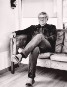 Henrik Lindberg, Inhaber von Lindberg, mit einem Lächeln auf einem typisch nordischen Sofa sitzend.