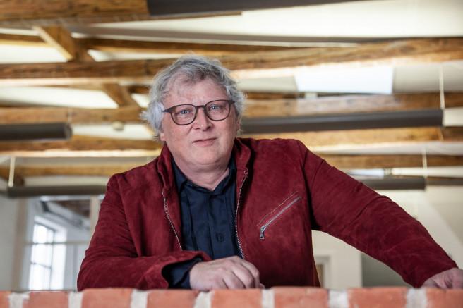 Henrik Lindberg mit roter Jacke und havannafarbener Acetatbrille auf einer Galerieebene in Lindberg Headquarter.