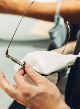 Eine BELLEVUE Mitarbeiter reinigt sorgfältig eine Metallbrille mit einem Mikrofasertuch.