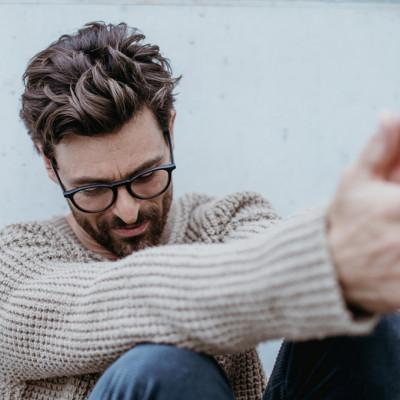 Man in naturfarbenen Wollpullover und schöner Brillenfassung in entspannter Haltung und einem Lächeln im Gesicht.