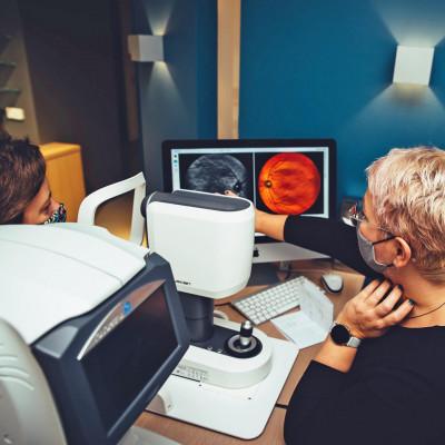 Augenoptikerin von BELLEVUE mit Kundin an einem Gerät zum Netzhaut-Scan. Die Optikerin erklärt das Abbild der Netzhaut auf dem Bildschirm.