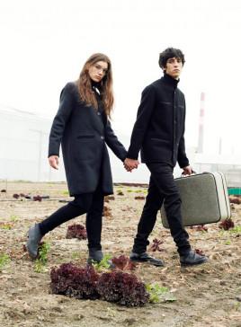 Ein junges brilletragendes Paar mit Koffer geht über eine urbane Sandfläche.