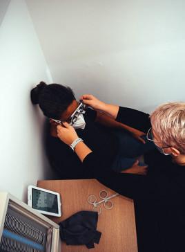 Augenoptiker mit Kundin beim Einstellen einer Sehtest-Prüfbrille im Augenprüfraum bei BELLEVUE.