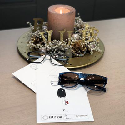 Adventsgesteck mit einer Kerze und BELLEVUE Schriftzug aus Holzbuchstaben sowie 2 Brillen und Geschenkgutscheinen.