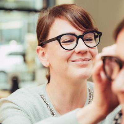 BELLEVUE Augenoptikerin überprüft den Sitz einer Brille am Kopf einer Kundin.
