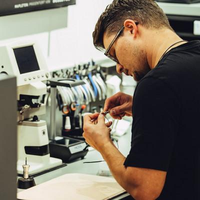 Augenoptiker in der Werkstatt beim Montieren einer Brille.