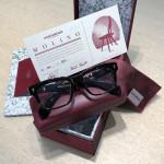 Arrangement der edlen Verpackung und des Zertifikats einer Jacques Marie Mage Brille im typischen bordeaux-rot.
